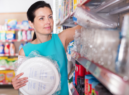 Portrait of female want to buying disposable tableware in a supermarket