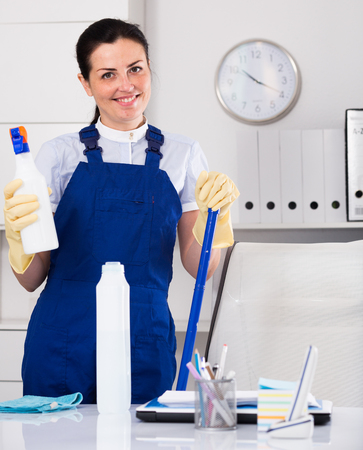 Cheerful female cleaning furniture in office with rag and cleanser