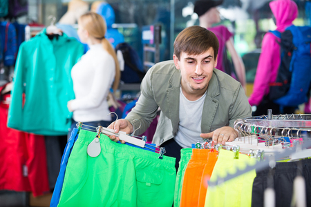 25 35: man gladly choosing a sport shorts in the shop Stock Photo