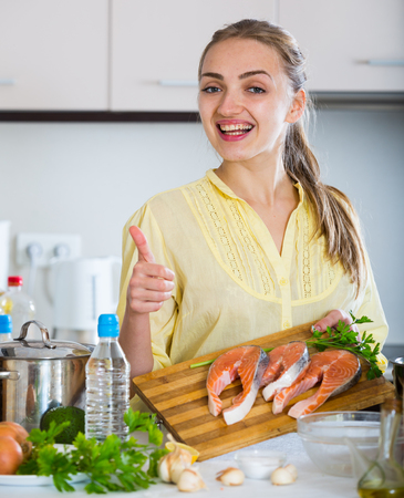 jorobado: Female with long hair preparing trout dish at home
