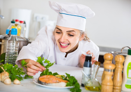jorobado: Happy young russian  cook with prepared salmon in professional kitchen