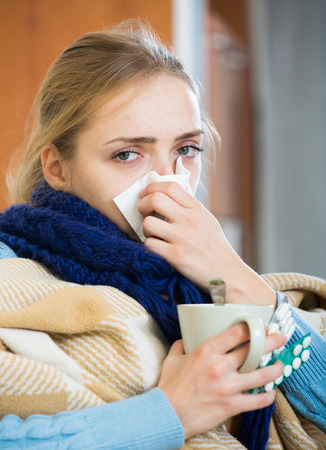 Young woman with cold and blocked nose at home