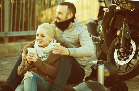 sandwitch: Young couple posing near motor bike with sandwitches and coffee