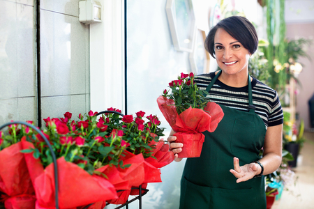 Cheerful positive  woman florist smiling among the potted plants in the floral shop Stock Photo