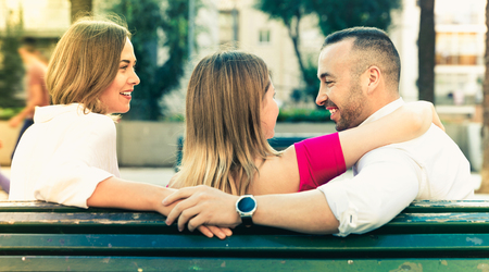 Image of the love triangle between young smiling cheerful positive people outdoor Stock Photo
