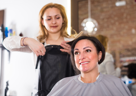 Hairdresser is doing hairstyle and cut by means of scissors and hairbrush for woman.  Stock Photo