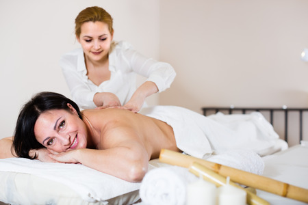 Laughing woman likes work of young masseur in spa salon and procedure of massage shoulder area
