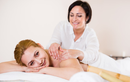 Young woman on massage procedure in Spa salon where bamboo sticks are used