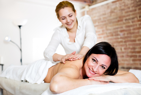 Positive adult woman very happy with procedure of massage in beauty parlor Stock Photo