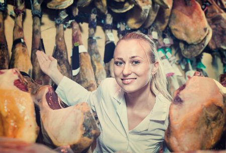 Friendly smiling young female seller wearing uniform working with iberian ham in meat shop Stock Photo