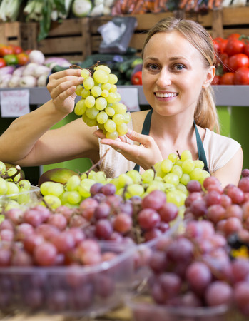 Portrait of cheerful smiling young woman in apron selling ripe grapes at fruit market