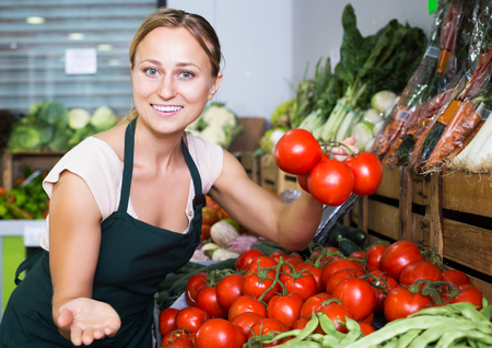 Portrait of young happy woman in apron selling organic tomatoes in shop Stock Photo