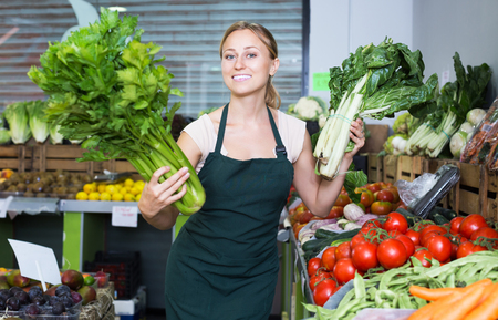 Glad girl seller wearing apron holding fresh celery and mangold on market