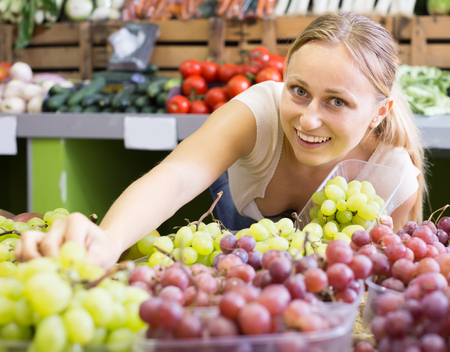 attentive young female seller wearing apron holding bunch of grapes on market  Stock Photo