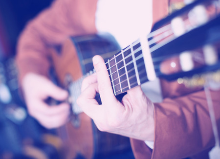 Image of hands of man in jacket playing an acoustic guitar