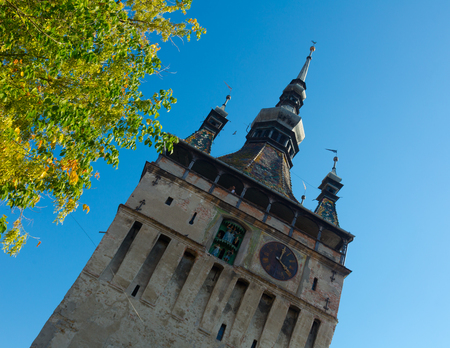 View of clock tower of Sighisoara against blue clear sky, Romania Stock Photo