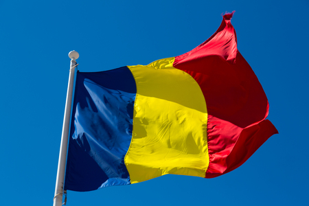 Romanian flag on flagpole waving against blue sky