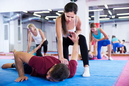 sporty girl is doing self-defence moves with coach in sporty gym.