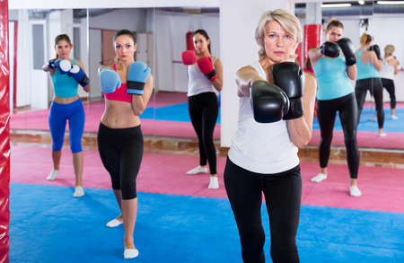 Portrait of concentrated mature female who is training box exercises with group in sporty gym