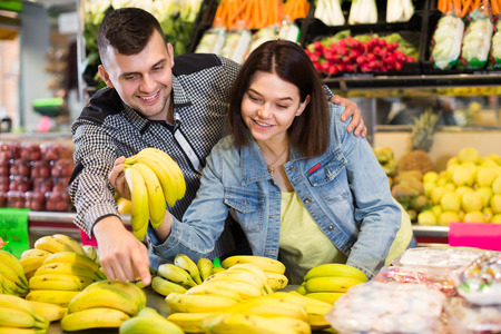 Young loving couple deciding on fruits in grocery shop