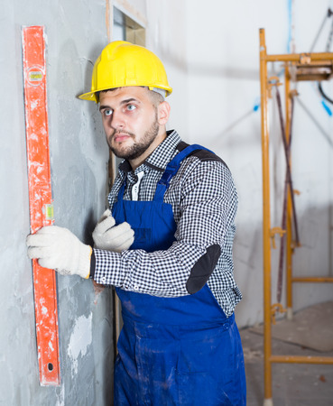 Professional worker in helmet is measuring wall with level.