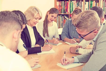 Happy students with female teacher studying in classroom 版權商用圖片