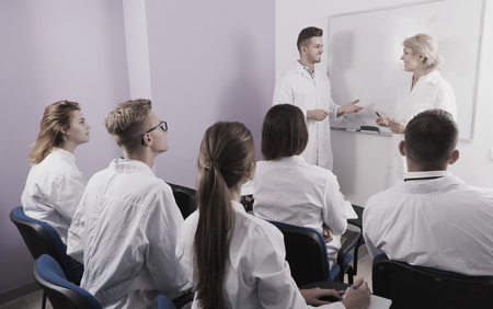 Young guy medical student talking with teacher in front of group of students in auditorium