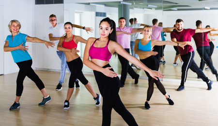 friendly men women of different ages posing in fitness studio