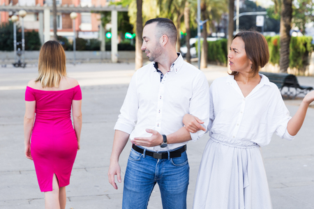 Man is fixing one is eyes on stranger woman and his girlfriend is angry on him on the street. Stock Photo