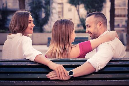 Imagen del triángulo de amor entre gente alegre al aire libre