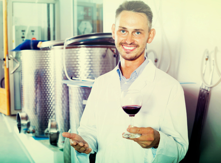 positive worker wearing white coat holding glass of wine in fermenting section