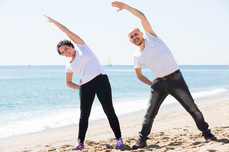 portrait of a happy mature couple training together by the sea