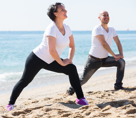 Cheerful smiling mature couple  in white t-shorts making exercises on the sandy beach. Focus on woman