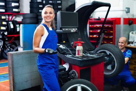 impact wrench: Young cheerful mechanic woman working on new tire fitting in service point Stock Photo