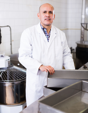 Middle aged smiling worker standing near the table in food manufacture Stock Photo