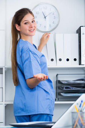 Smiling attractive female doctor searching patient history on shelves in office Stock Photo