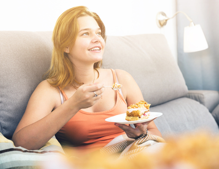 Cheerful young female eating sweet cake at home on  cozy sofa