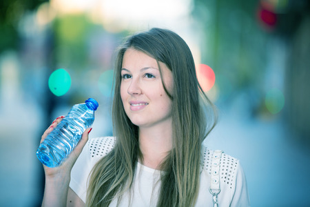 Attractive girl drinking water during walk around city in hot summer day