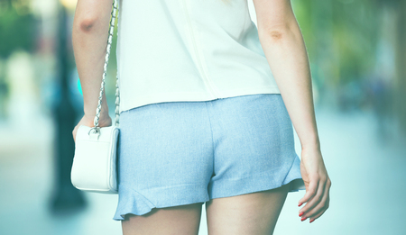 Close-up of female buttocks in blue short shorts on blurred cityscape background