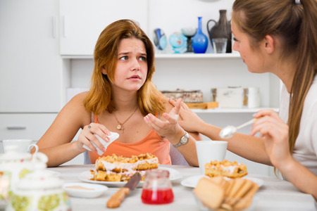 Portrait of female talking with sad girl friend at the kitchen Stock Photo