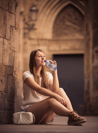 Young woman quenching thirst with water while sitting near old stone cathedral wall Stock Photo