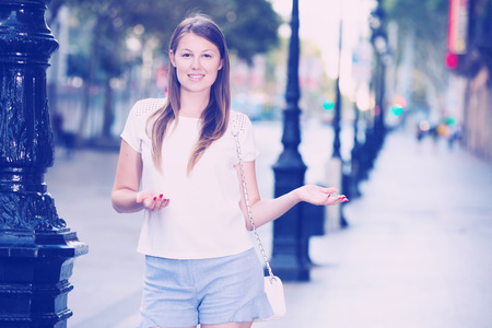 Positive young woman walking around city presenting or showing something