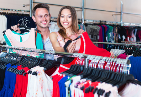 Husband and wife are choosing dress for her in boutique.