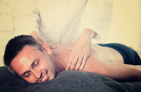 Woman  massaging a brunette guy at spa complex Stock Photo