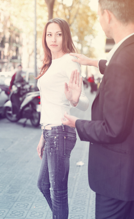 Young woman stopping stranger man bothering her on city street  Stock Photo