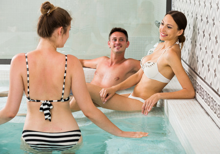 Young happy people relaxing in hot tub in spa Stock Photo