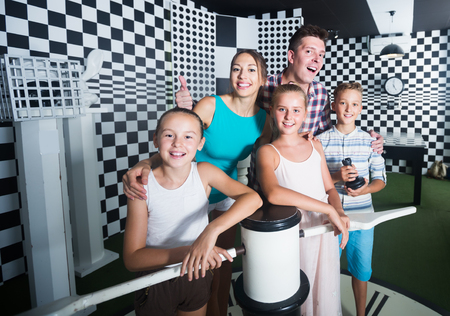 Smiling family is visiting of escaperoom stylized under chessboard