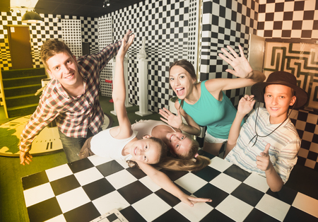 Ordinary family is visiting of escaperoom stylized under chessboard