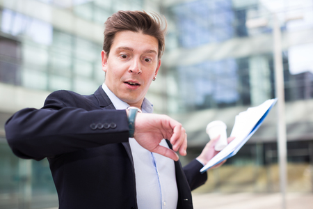Businessman hurrying to meeting and watching on wristwatch Stock Photo