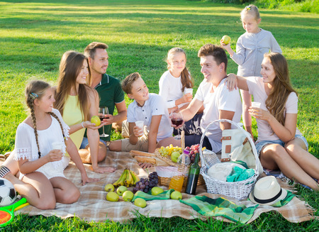 Group of laughing people with kids enjoying picnic on green meadow together